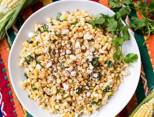 Mexican Corn Salad - Fresh corn tossed with homemade mayo, lime juice and cojita cheese and sprinkled with chili pepper. An authentic, easy side dish!