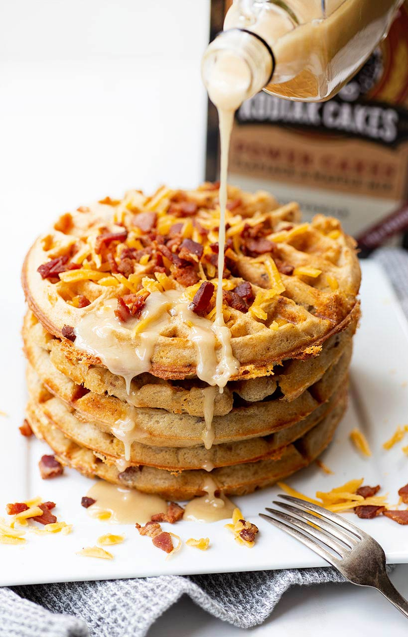 Bacon Cheddar Waffles with Maple Glaze - fluffy waffles cooked to crispy perfection, packed full of savory bacon and chees and drizzled with a maple glaze.