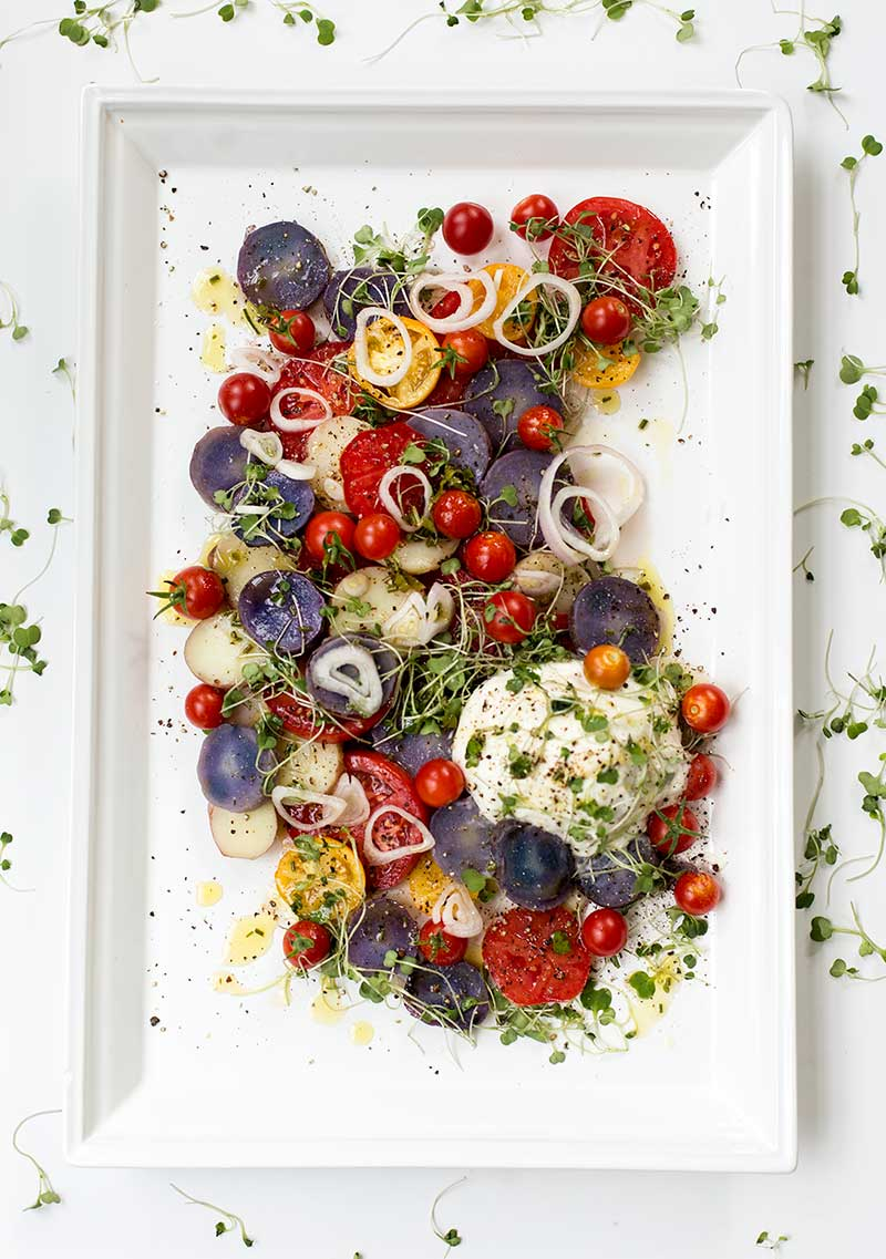Herbed Potato Salad with Fresh Tomatoes and Burrata: Fresh tomatoes, purple potatoes and creamy burrata cheese topped with microgreens and herb vinaigrette.