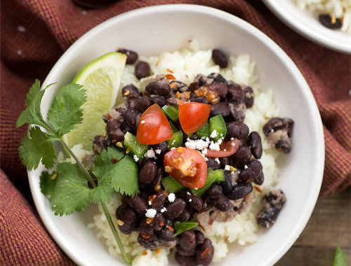 Cuban Black Beans and Rice: Black beans sauteed with onions, peppers, garlic and spices, served over white rice and finished with a splash of vinegar.