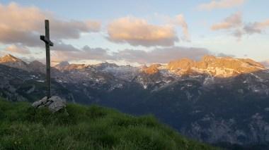 Gipfelkreuz, im Hintergrund erste Sonnenstrahlen auf dem Funtenseetauern und anderen Gipfeln des Steinernen Meeres