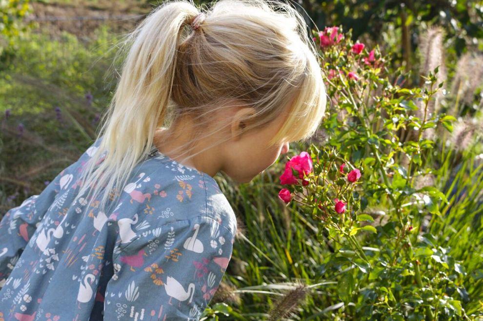 Mädchen riecht an Blume