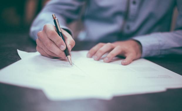 Człowiek podpisujący dokument