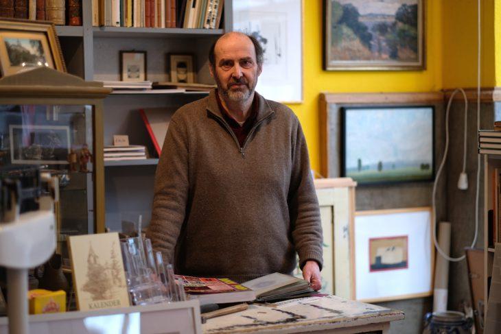 Markenzeichen Wollpullover: Helmut van Bebber am Tresen seines Ladenlokals in der Herzogstraße, vor sich ein paar Singles – ein Bild, das es nicht mehr lange geben wird