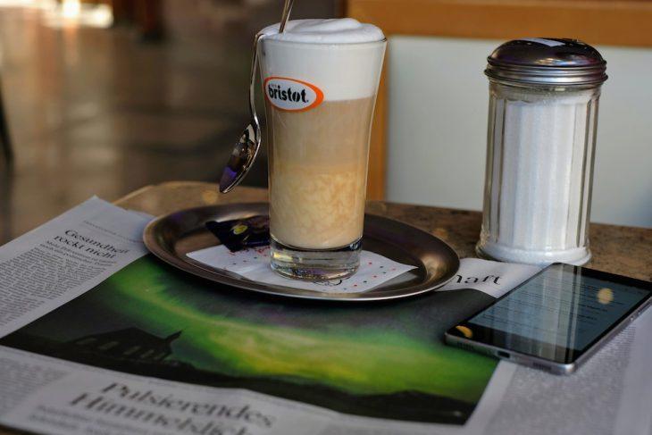 Eine deutsche Zeitung, die ein Polarlicht aus Island zeigt, als Unterlage für ein italienisches Getränk und ein chinesisches Mobiltelefon, auf dem als App ein Newsreader aus Frankreich läuft, aufgenommen mit einer Kamera aus Japan – und das in einem Eistempel unter griechischer Führung. Unser Leben ist schon sehr international geworden. Aber der Zucker könnte aus Kalkar stammen
