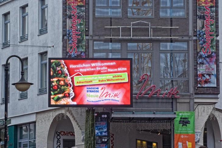 LED, Banner, Neonreklame, Lichterketten, noch mehr Banner – der Eingang der Neuen Mitte (Foto © Kleinendonk)