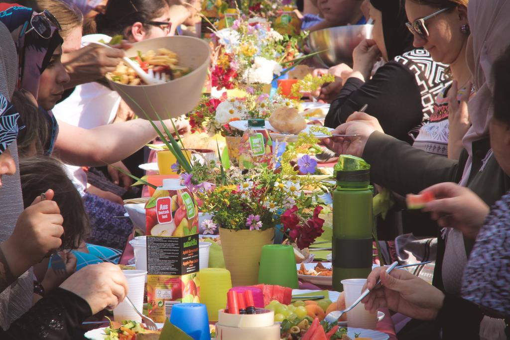 Menschen verschiedner Nationen sitzen an einem bunt gedeckten Tisch und Essen.