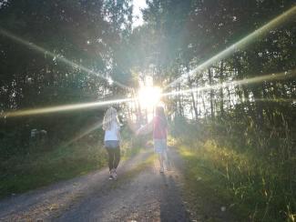 Zwei Mädchen gehen der Sonne auf einem Waldweg entgegen.