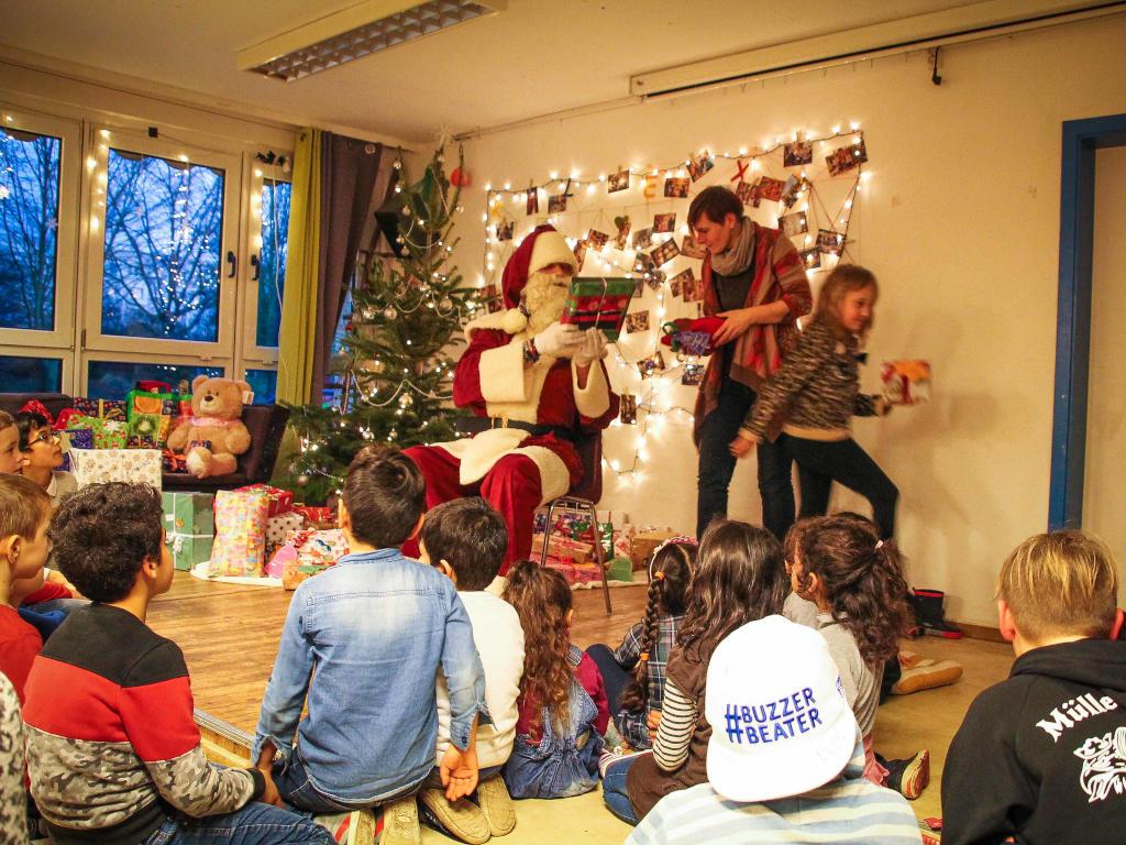 Der Weihnachtsmann verteilt Geschenke an Kinder und Erwachsene.