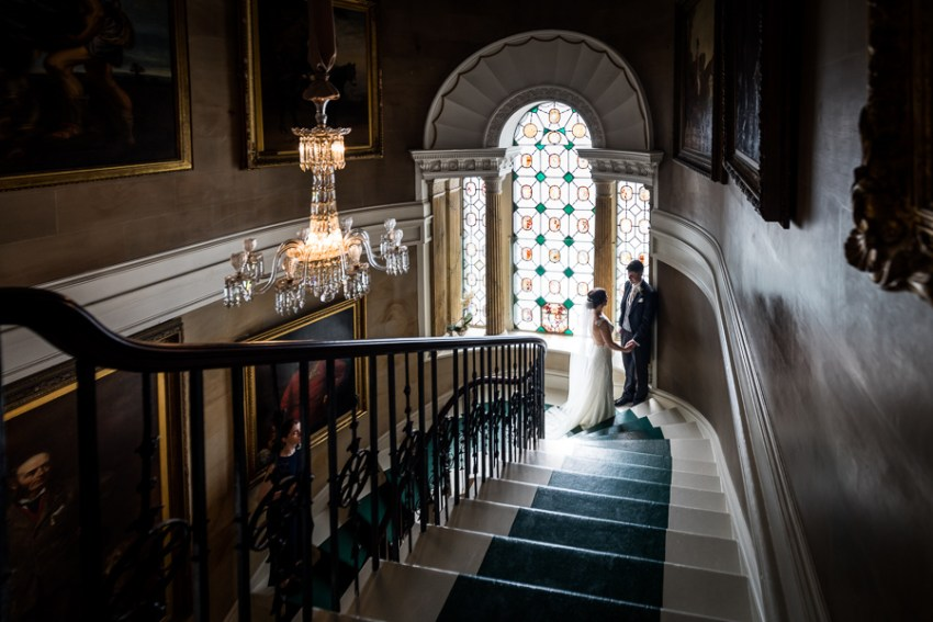 bride and groom on the grand staircase at ripley castle