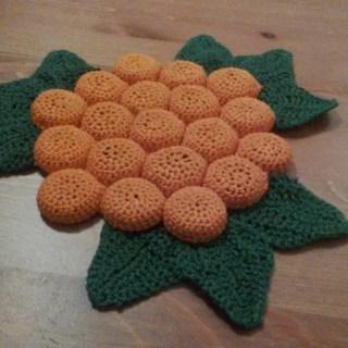 A trivet made of crocheted bottle caps