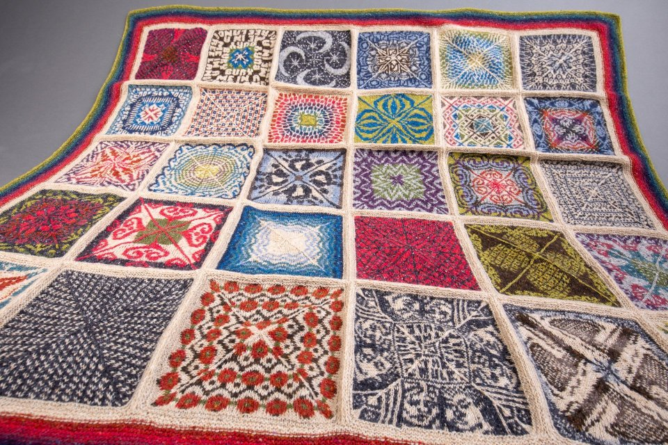 knitted blanket comprised of complex stranded colourwork squares