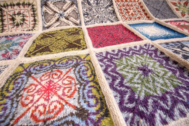 a multicoloured blanket comprised of stranded colourwork squares, photographed from a dramatic angle