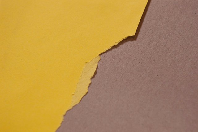Torn yellow envelope front across the board backing of a DO NOT BEND envelope construction