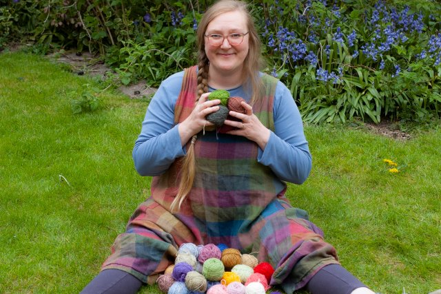 Felix sits on the ground with a lap full of balls of yarn, grinning. She is wearing a brightly-coloured Playsuit from The Slow Wardrobe, grinning