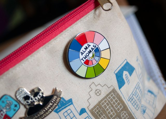 canvas pencil case featuring Dutch buildings and a lovely bright red zipper; pinned onto the pencil case is a vibrant circular enamel pin featuring a colourwheel design inspired by the lovely bright shades so often used by the American Artist, Alma Thomas whose name appears at the centre of the pin.