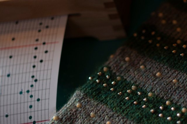 mysterious closeup of punch-card next to detail of beaded knitting, where beads placed in the knitting speak to the notes placed on the grid of the punch-card