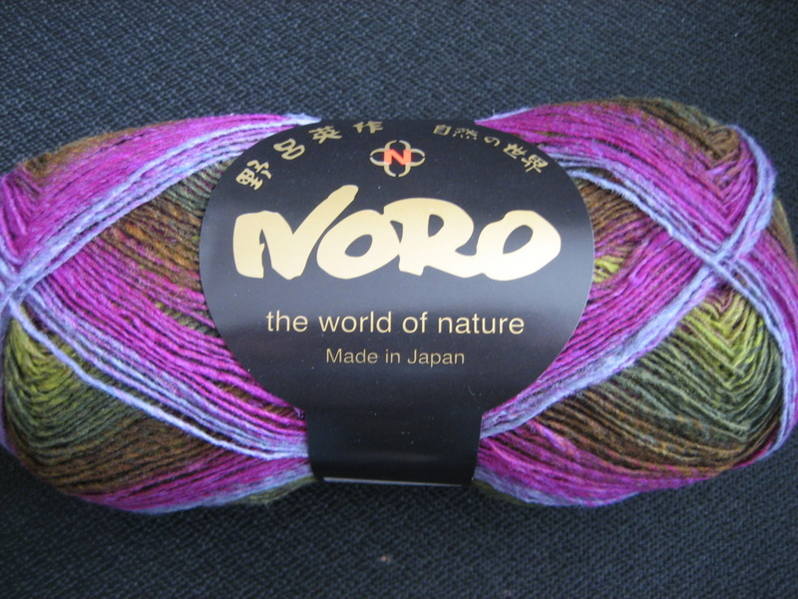 A ball of Noro Kureyon Sock yarn in purples and greens.