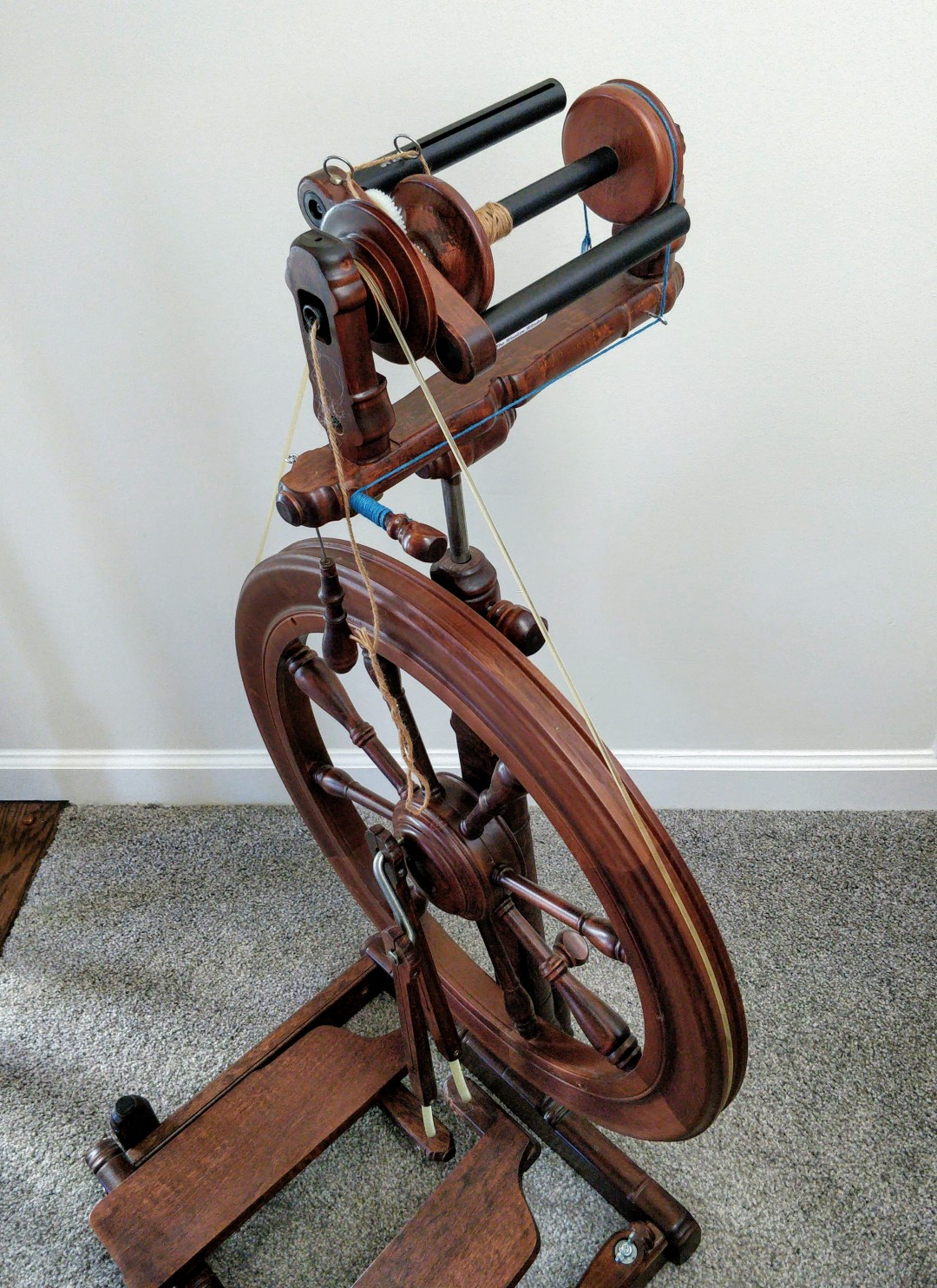 A Kromski Sonata spinning wheel in walnut finish, in 3/4 view from above, with a Woolee Winder flyer and bobbin visible.