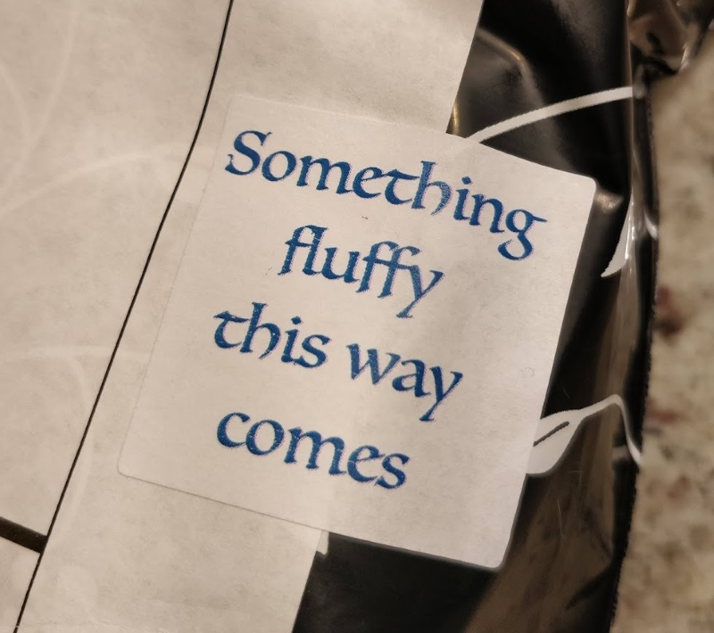 "A sticker on the outside of a shipping bag that says, in fancy blue type, ""Something fluffy this way comes"""