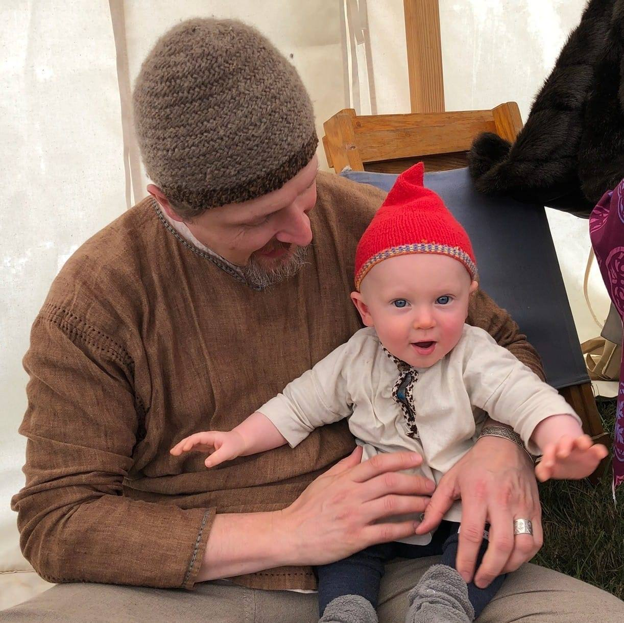 A baby sits on his father's lap, wearing a beige tunic and a bright red hand-knit hat with a pointy top.
