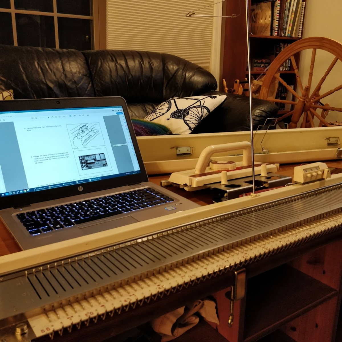 The knitting machine on my coffee table, with my laptop behind it. The user manual is displayed on the laptop screen.