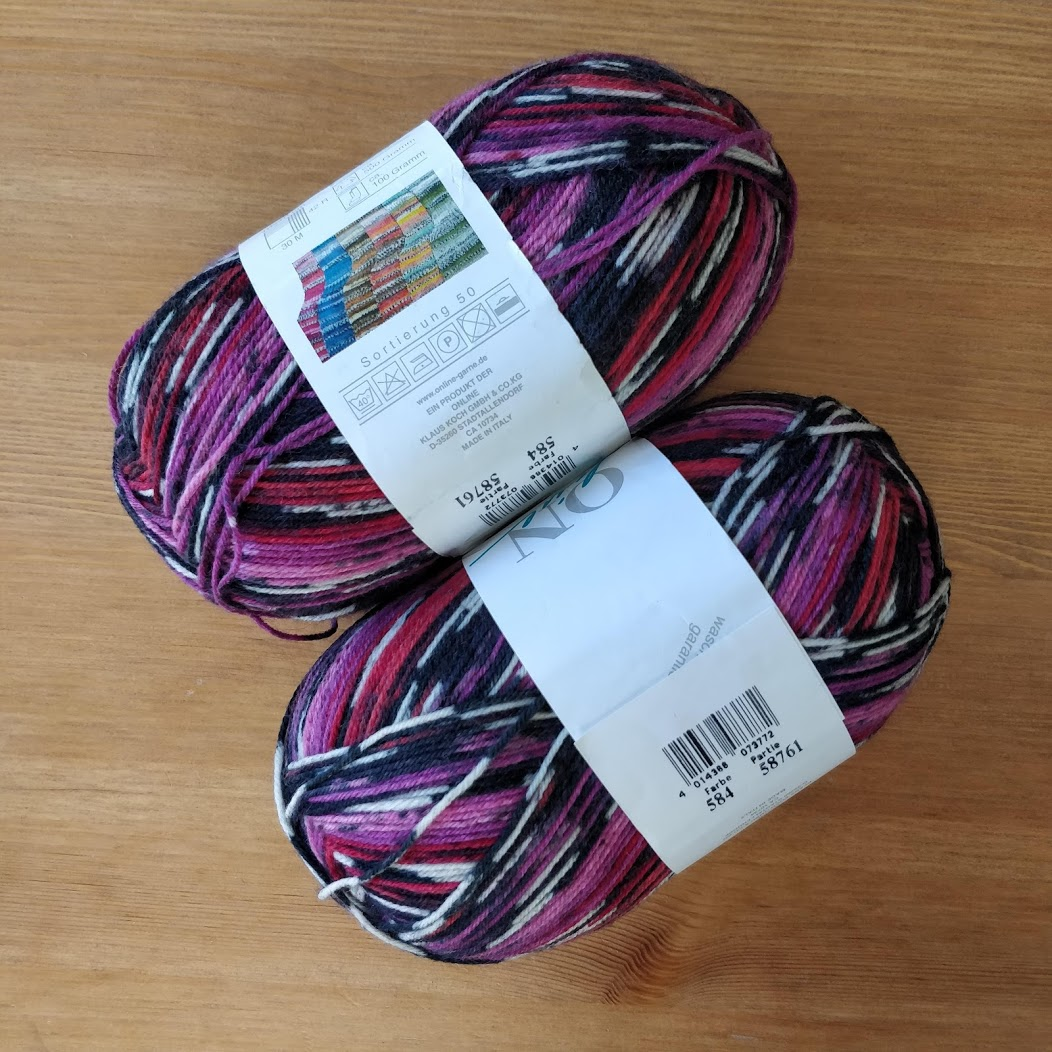 Two balls of self-striping pink and black sock yarn.