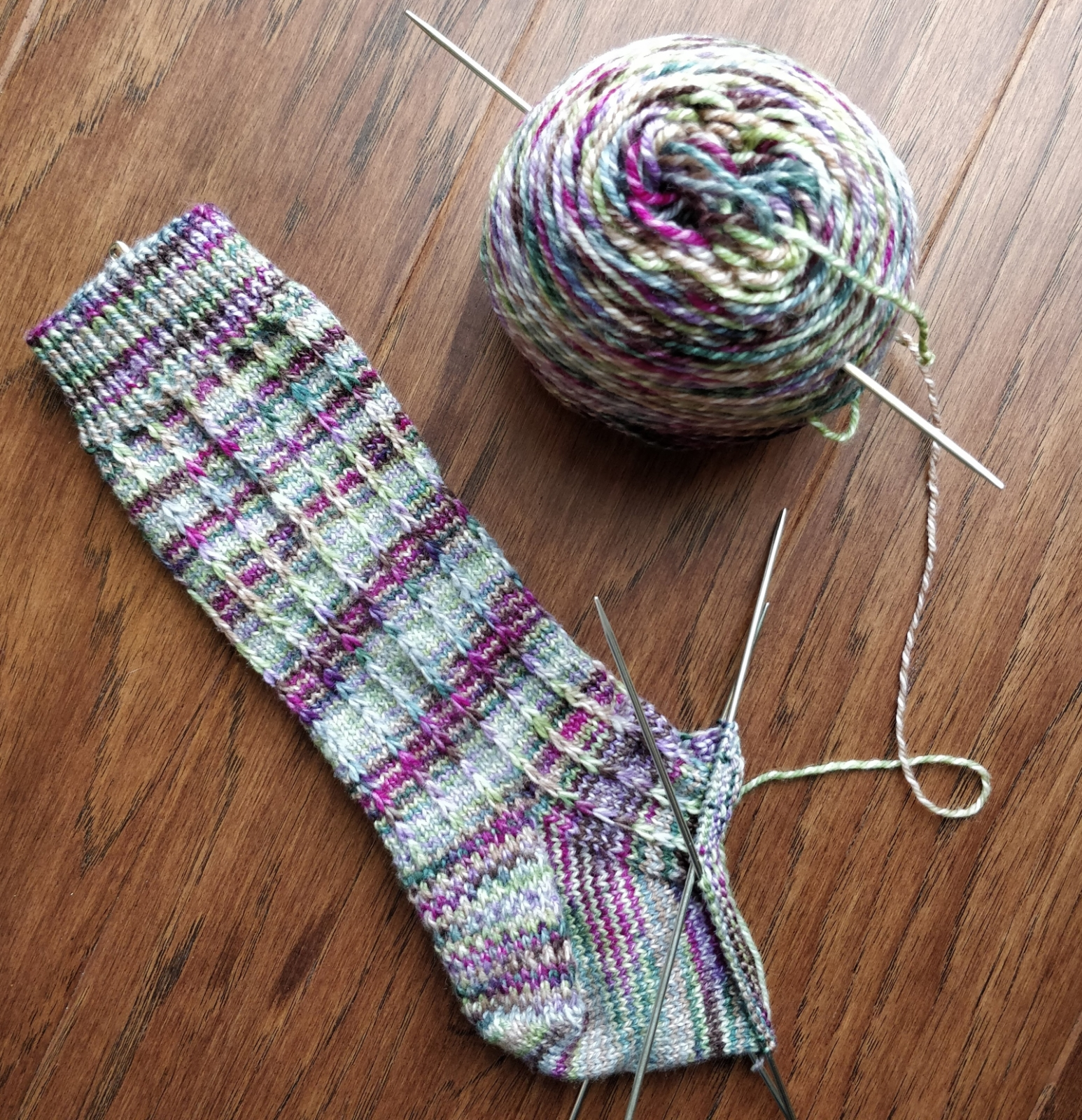 A half-finished sock with a half-finished ball of yarn on a wooden floor. The sock has spirals of pooling colour, pinks and purples over blue, sand, and green.
