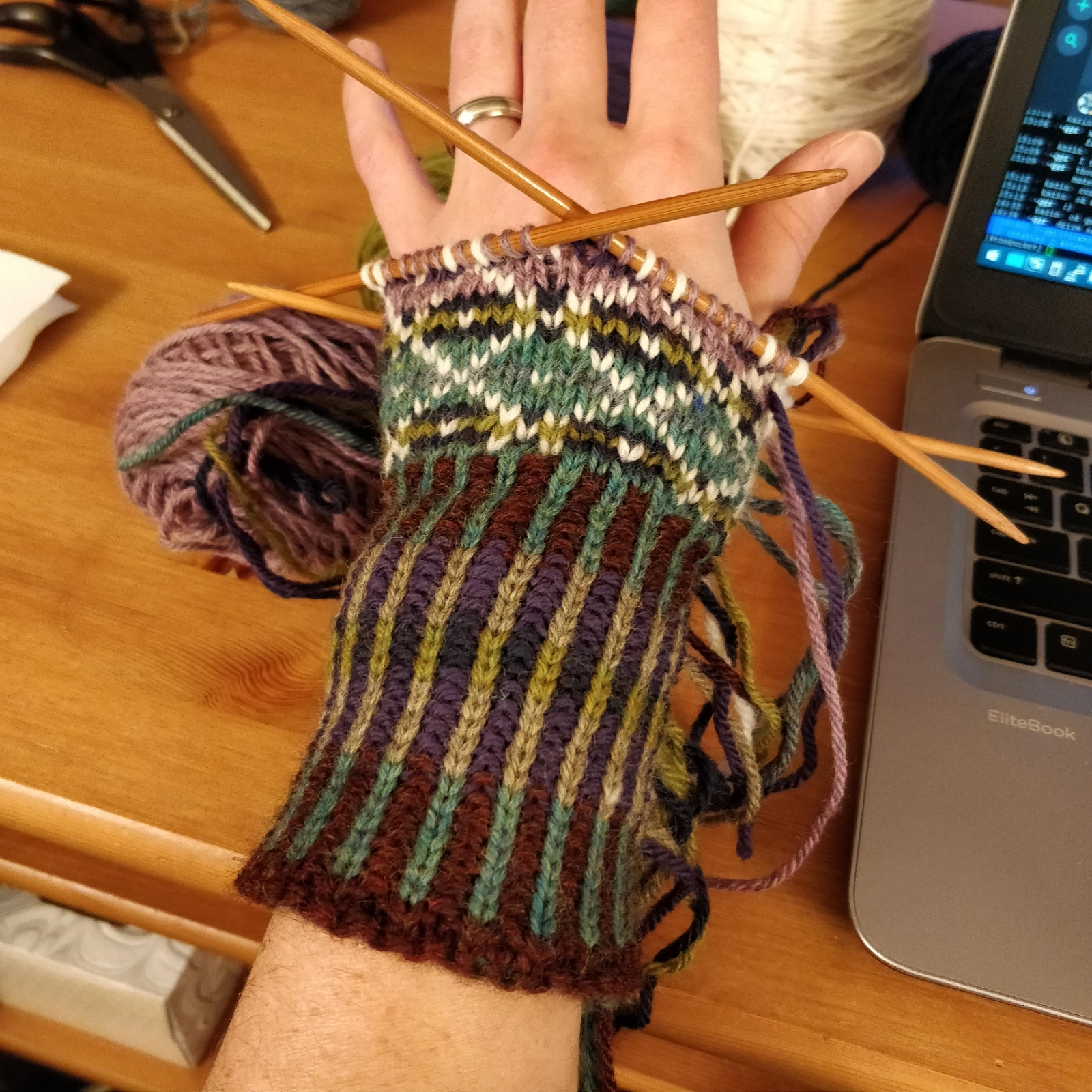 The back side of a colourwork mitten in progress.