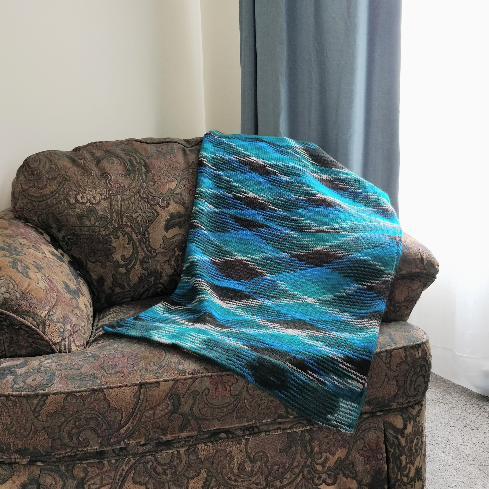 A teal and brown knit wrap draped artfully on an oversized, overstuffed chair.