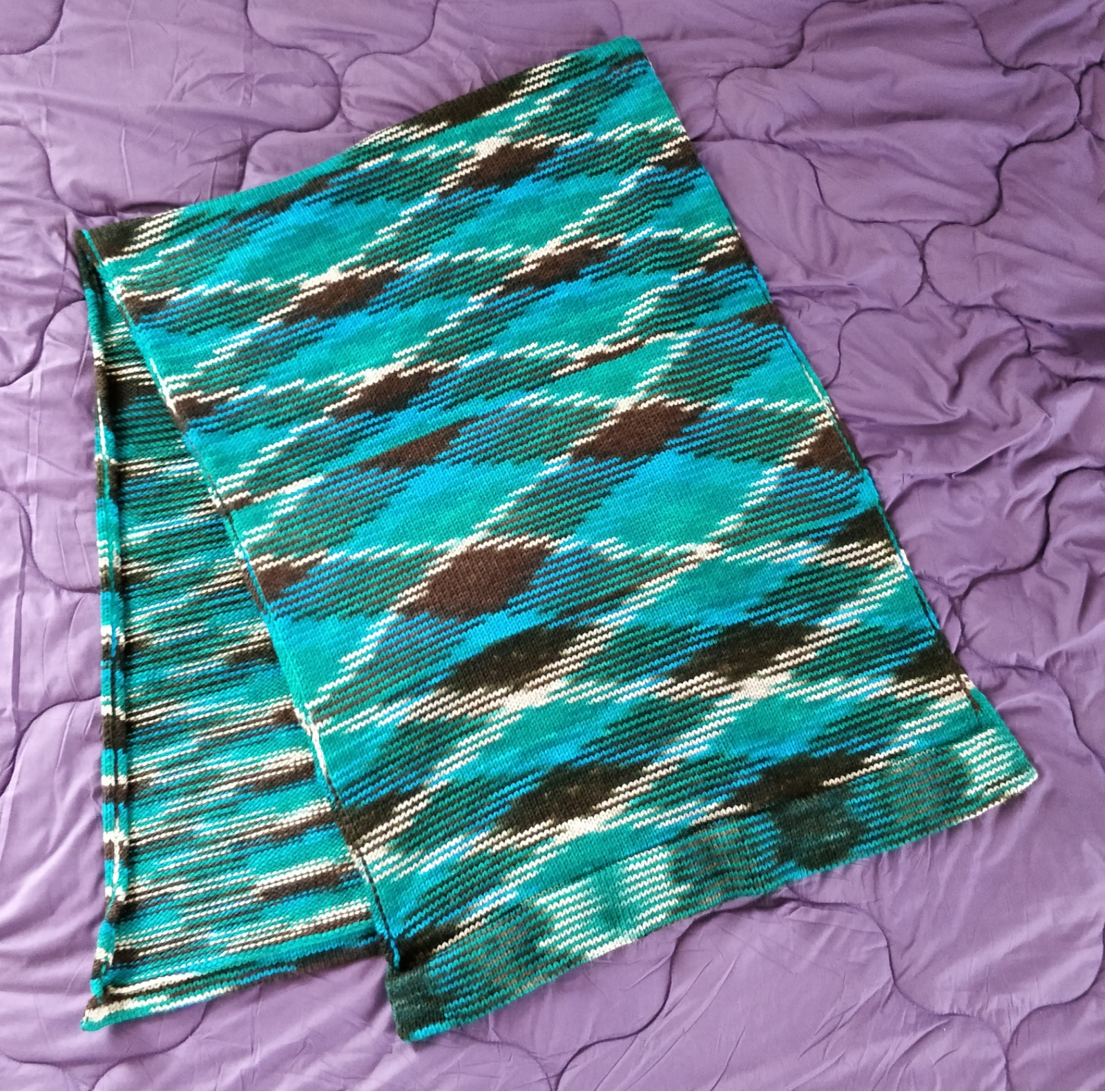 A teal and brown knit wrap displayed on a purple bedspread.