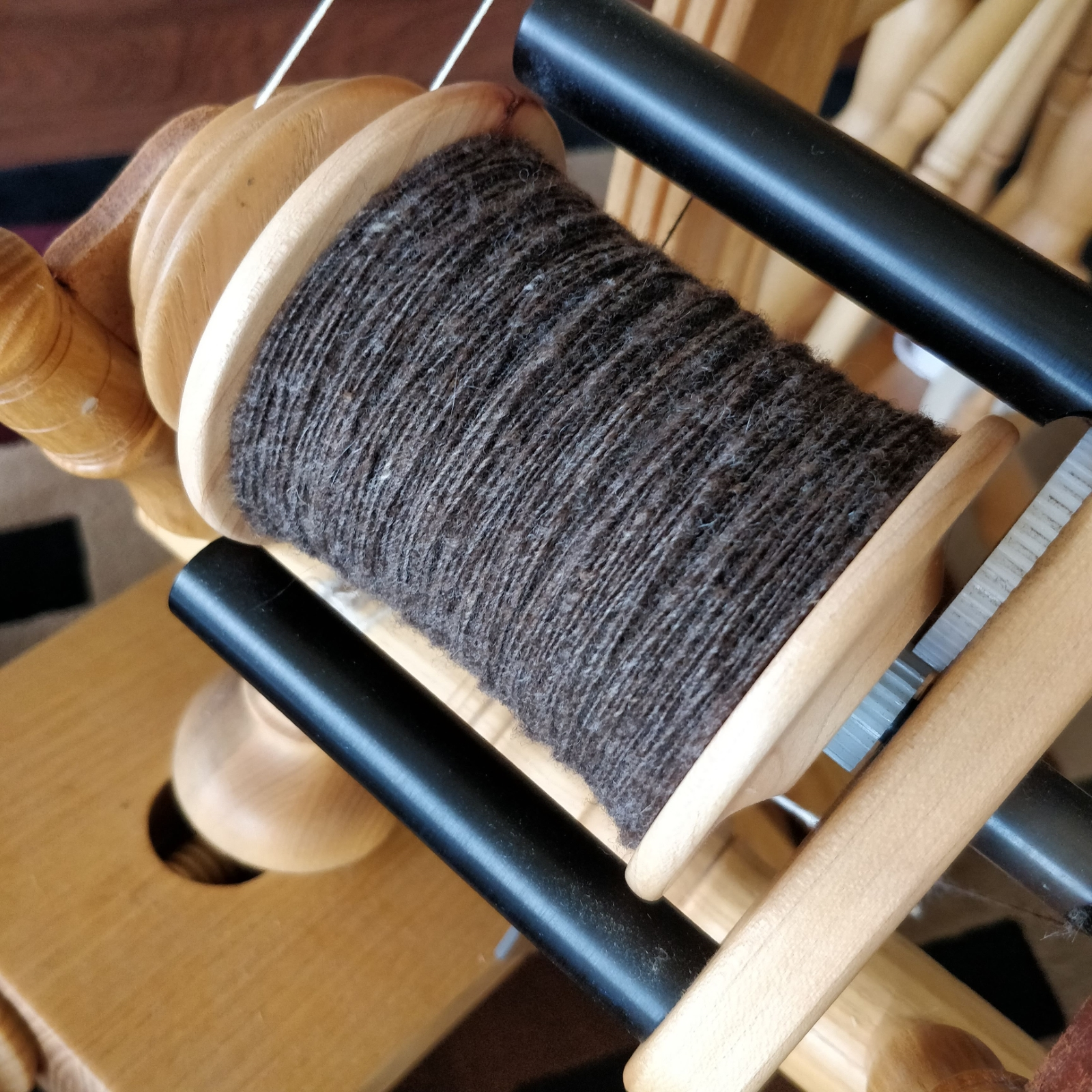 An almost-full bobbin of fine brown single-ply yarn, still on the spinning wheel.