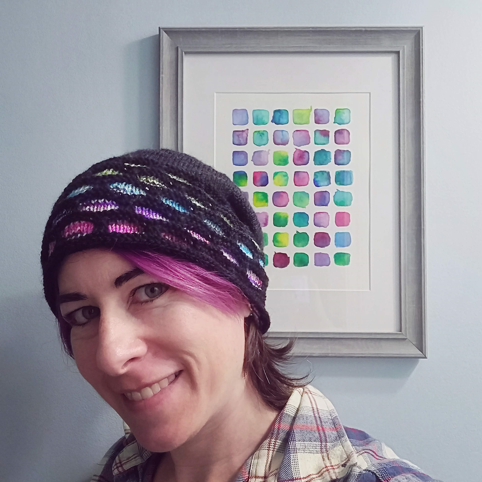 Pirate modeling the Which Scraps Hat in front of a watercolour painting that matches its rainbow colours