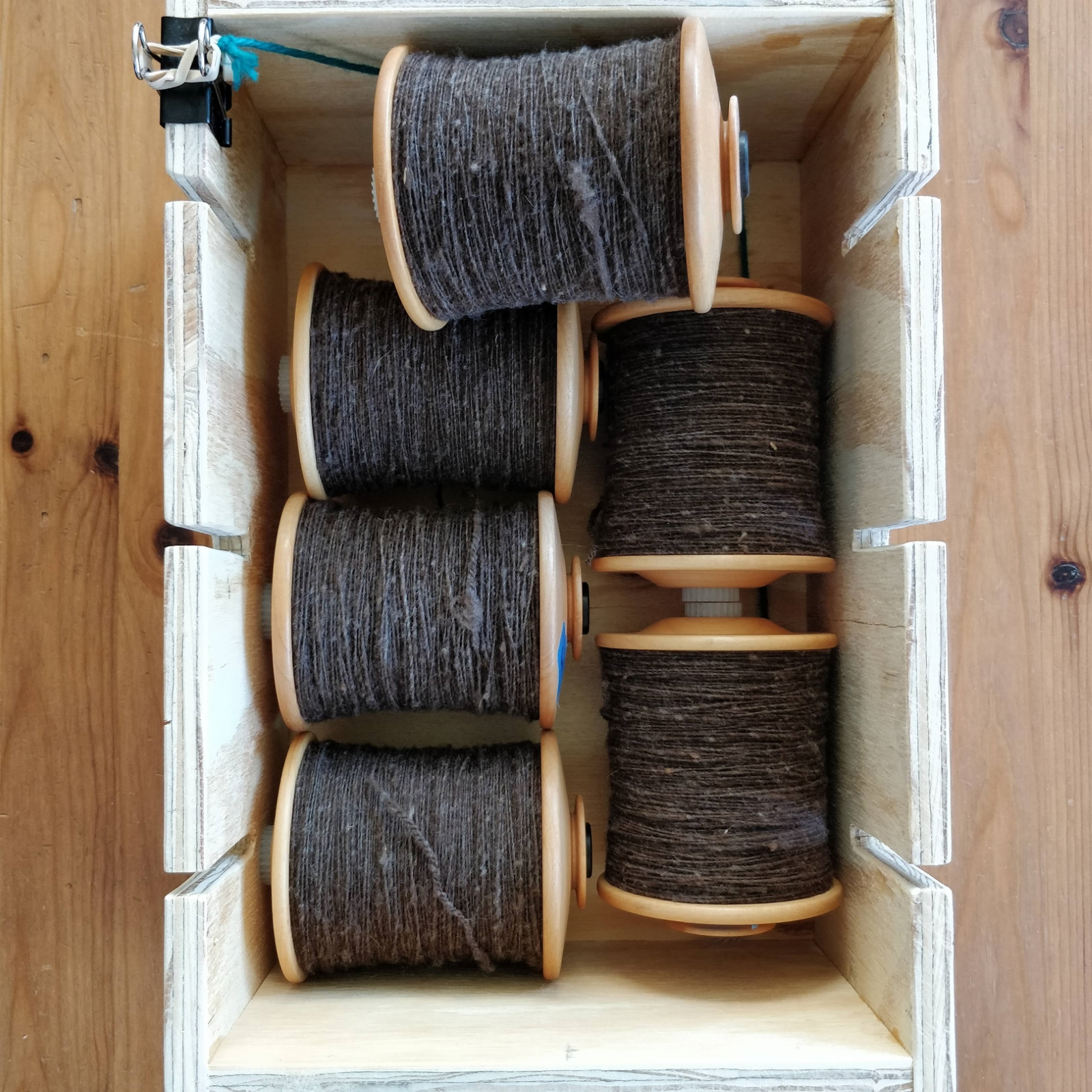 Six full bobbins of singles sit inside a plywood box.