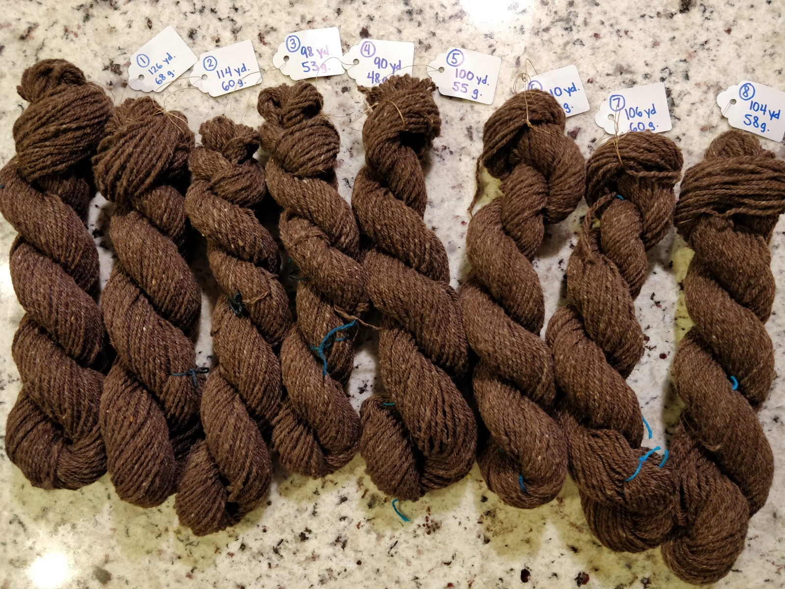 Eight hanks of brown three-ply yarn sit on a stone countertop.