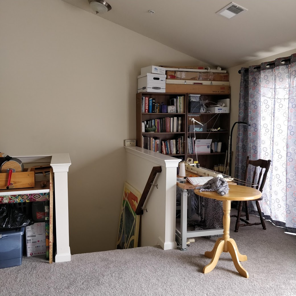 A view of the knitting machine corner that shows the stairs, the half-wall behind the knitting machine table, two bookcases against the wall, and a sliding glass door covered by a curtain.