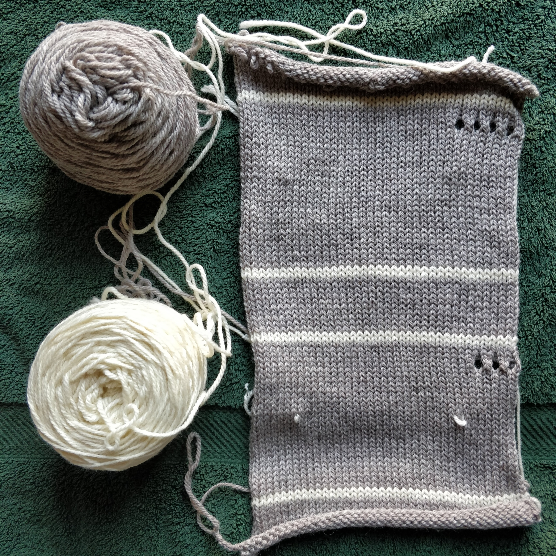 A gauge swatch of grayish-tan yarn with stripes of white to delineate sections of different stitch sizes.
