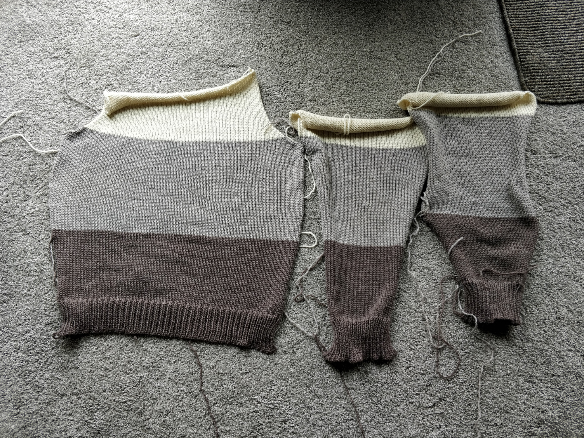 The back and two sleeves of a colourblock sweater - cream at the top, light grayish tan in the middle, and darker brown at the bottom.