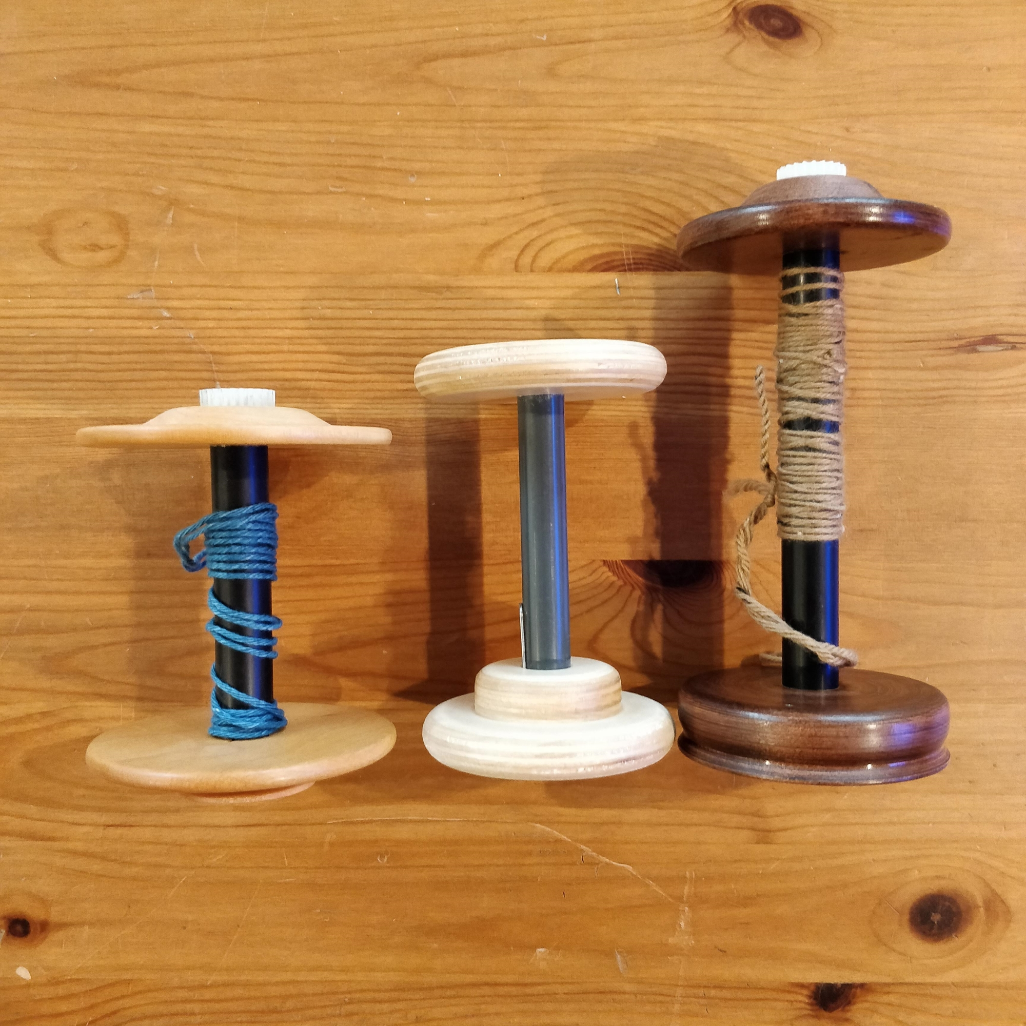Three bobbins, compared in length. The Schacht-Reeves bobbin on the left is the shortest; the Spinolution bobbin in the center is a little bit longer; the Kromski bobbin on the right is significantly longer.