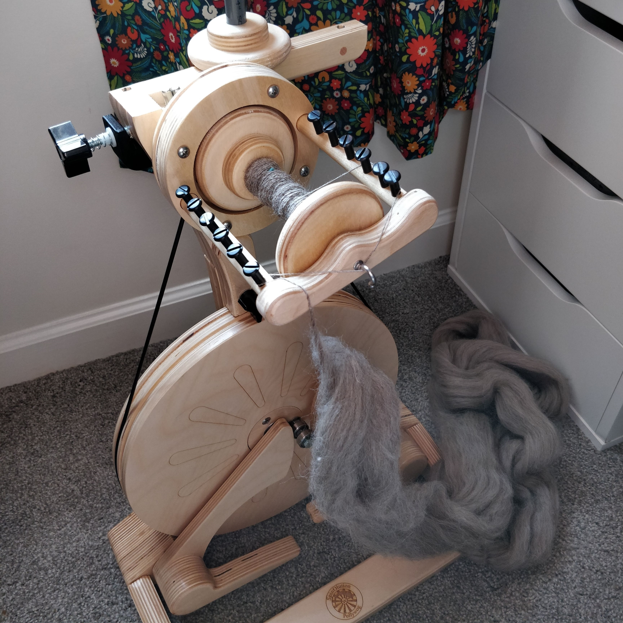 The Pollywog wheel with a little bit of gray yarn spun onto the bobbin and a lot of gray fibre hanging down from the orifice hook.