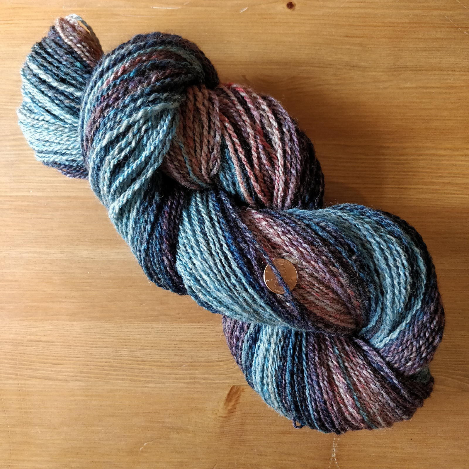 A skein of handspun yarn sits on a wooden table. It is spun in a gradient of medium pink through dark purple and dark blue to light blue.