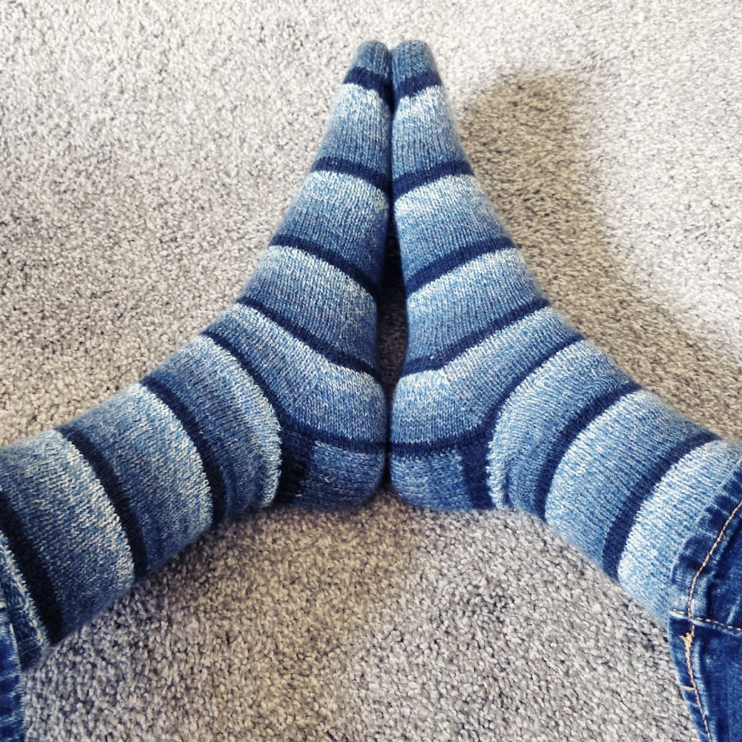 """Pirate's feet modeling the """"Got the Blues"""" socks, knit in gradiated shading stripes of dark to light blue."""