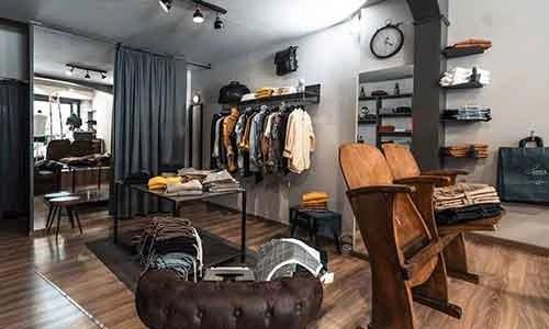 negozio abbigliamento uomo; stand pieni di vestiti e due sedie di legno in primo piano