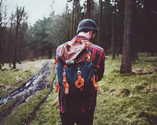 ragazzo nel bosco di schiena, che indossa una camicia boscaiola rossa e nera
