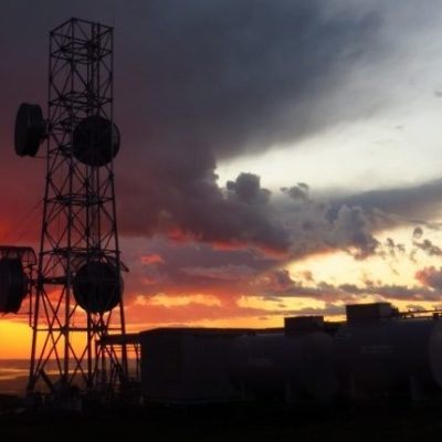 A GCI telecommunications tower in rural Alaska, silhouetted by a fiery sunset