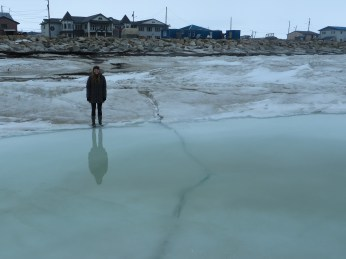 Standing next to a crack in the sea ice on an evening excursion. (Photo: Laura Kraegel, KNOM)