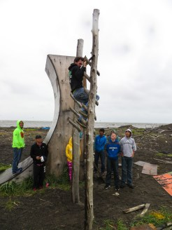 Nick Hanson practices the salmon ladder obstacle on the course he built out of driftwood. Photo: Laura Kraegel, KNOM.