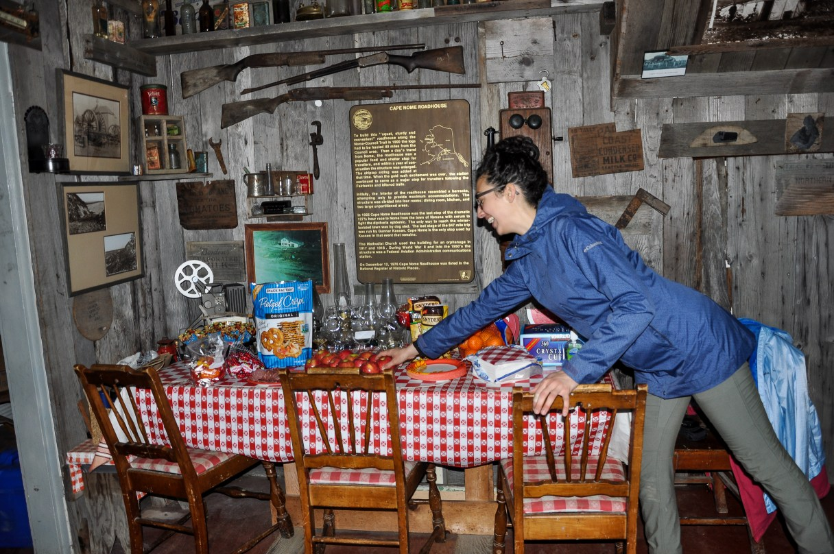 Margaret prepares the supper table with food cooked on a camp stove in a cabin without running water.
