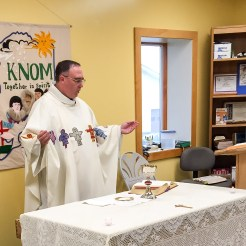 On dedication day, Father Ross Tozzi celebrates Mass in KNOM's lobby.
