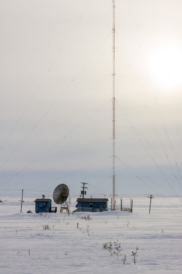 The KNOM AM transmitter tower in an open, snow-covered field.